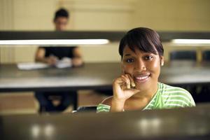 biblioteca da faculdade e aluna, mulher negra, olhando para camer foto