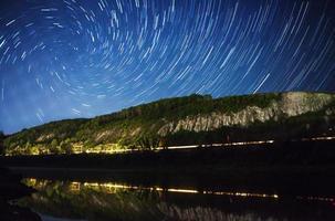 lindo céu noturno, via láctea, trilhas e árvores em espiral foto