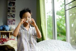 menino beber água de vidro foto