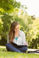 estudante universitário sorridente, sentado e escrevendo no bloco de notas