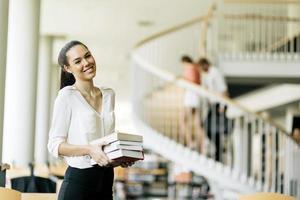 linda mulher segurando livros em uma biblioteca foto