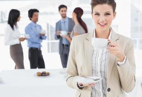 empresária sorridente com uma bebida foto