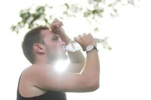 corredor masculino bebendo água mineral