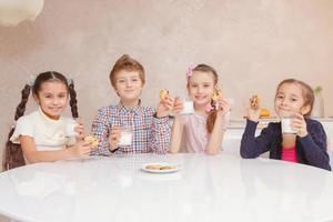 crianças bebem leite com biscoitos