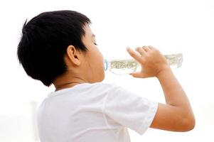 menino bebe água da garrafa foto