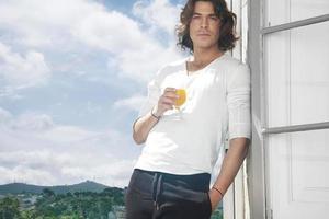homem bebendo suco. vista da montanha foto