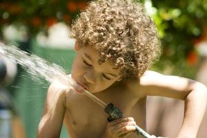 menino beber água de mangueira foto