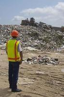 trabalhador assistindo escavadeira movendo resíduos no aterro foto