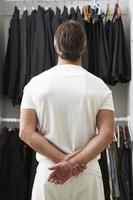 homem de pé na frente do guarda-roupa escolhendo roupas
