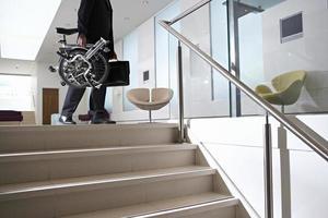 empresário carregando bicicleta e maleta etapas acima foto