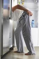 homem invadindo a geladeira à noite foto
