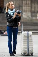 mulher andando na cidade de outono com câmera digital foto