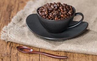 grãos de café em uma xícara de café de saco foto
