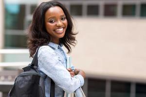 jovem estudante universitária africana segurando livros foto