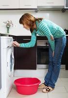 mulher com máquina de lavar roupa foto