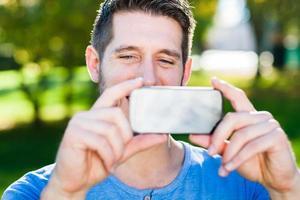 jovem está tomando uma pciture com seu telefone inteligente foto