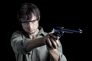 homem no campo de tiro com revólver foto