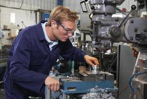 engenheiro usando broca na fábrica foto