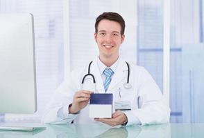 médico, segurando a caixa do medicamento no hospital foto