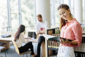 linda mulher lendo um livro em uma biblioteca foto