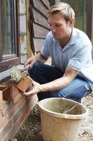 trabalhador da construção civil colocando tijolos foto