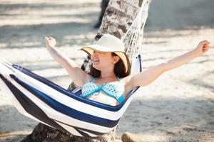 mulher, estendendo-se na rede na praia