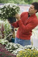 homem no topo de compras de flores no centro de jardim foto