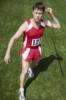 atleta masculino segurando o dardo foto