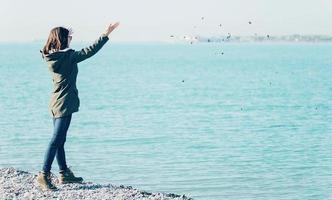 jovem mulher jogando pedras no mar foto