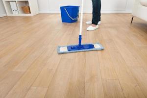 mulher limpando o chão de madeira em casa foto