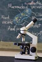 microscópio da velha escola na sala de aula com quadro-negro