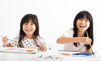 crianças felizes pintando na sala de aula foto