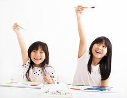 crianças felizes pintando na sala de aula