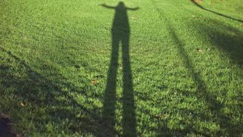 sombra de silhueta de menina na grama foto
