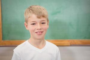 estudante sorridente na frente do quadro-negro