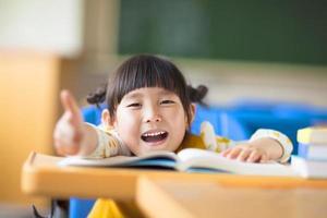 criança feliz polegar para cima com livro foto