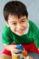 garotinho, construindo uma casa pequena com blocos de madeira coloridos foto