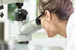 mulher que trabalha com microscópio