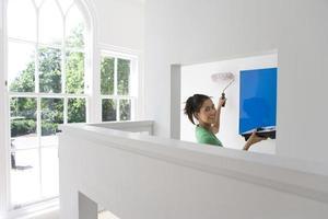 jovem mulher com bandeja e rolo de parede de pintura, sorrindo, portrai