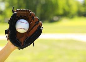 mão do pagador de beisebol com luva e bola sobre o campo foto