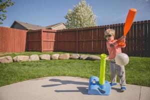 menino jogando t-ball foto
