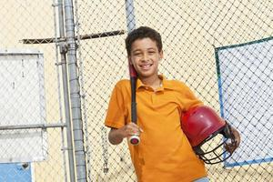 menino em uma gaiola de rebatidas foto