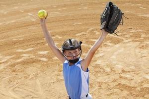 jogador de softbol entrando no campo com os braços levantados foto