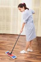 jovem empregada limpando chão foto
