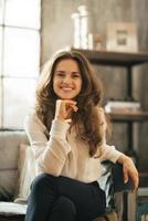 mulher jovem sorridente, sentada no sofá no apartamento loft