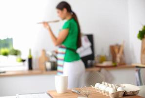 mulher jovem sorridente na cozinha, isolada no fundo