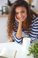mulher jovem sorridente na cozinha, isolada no fundo foto
