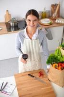 mulher fazendo comida saudável em pé sorrindo na cozinha foto