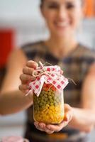closeup em jovem dona de casa mostrando o frasco com legumes em conserva