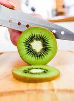mãos de mulher cortando kiwi
